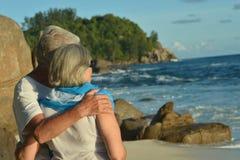 Elderly couple standing on sandy beach. Rear view of elderly couple standing on sandy beach during sunset Stock Photography