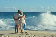 Elderly couple standing on sandy beach. Rear view of elderly couple standing on sandy beach during sunset Royalty Free Stock Photos