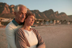 Elderly couple standing together and embracing on the beach. Portrait of elderly couple standing together and embracing on the beach. Senior men embracing his Royalty Free Stock Photo