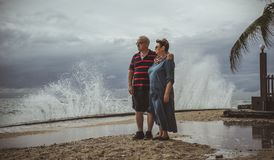 An elderly couple stands on the beach and watching as the approaching storm into the waves. Stock Photography