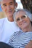 Elderly couple stood by tree royalty free stock image