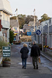 Elderly couple strolling down a quiet, empty street Stock Photo