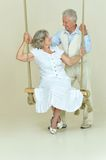 Elderly couple on swing Stock Images