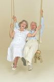 Elderly couple on swing Royalty Free Stock Photography