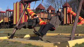 Elderly couple swinging at playground, child coming to his grandparents. UHD 4K stock video