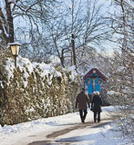 Elderly couple take a walk on a snow path with small chapel in w Royalty Free Stock Photo