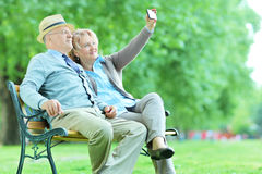 Elderly couple taking a selfie in the park stock image