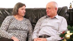 Elderly couple talking near Christmas tree stock video
