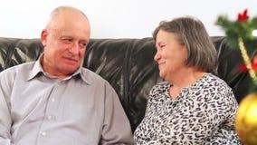 Elderly couple talking near Christmas tree stock video footage
