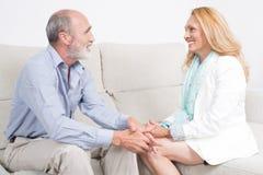 Elderly couple talking and smiling Stock Photo