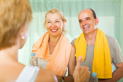 Elderly couple talking to trainer Stock Image