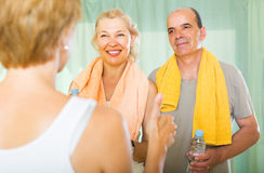 Elderly couple talking to trainer Stock Images