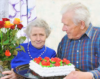 Elderly couple with tasty big cake Royalty Free Stock Photos