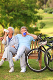 Elderly couple with their bikes. In the park royalty free stock photography