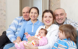 Elderly couple with their offspring. Happy elderly couple with their offspring at home Royalty Free Stock Images