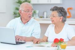 Elderly couple using computer. Elderly Stock Photos