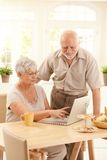 Elderly couple using computer. Smiling elderly couple using laptop computer in dining room, smiling, wife pointing at screen Royalty Free Stock Photography