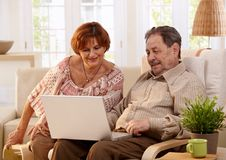 Elderly couple using computer computer Stock Photos