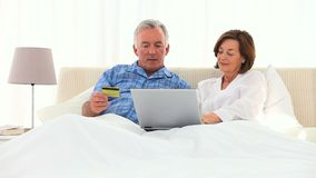 Elderly couple using a credit card on the internet Stock Photo