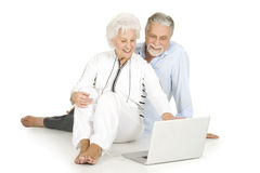 Elderly couple using laptop. In a white background Stock Photo