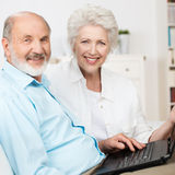 Elderly couple using a laptop computer. As they sit side by side on a couch sharing the internet and smiling at the camera Royalty Free Stock Photo