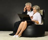 Elderly couple using laptop Stock Images