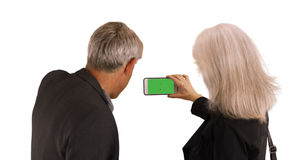 Elderly couple using smartphone to take pictures on white background Royalty Free Stock Photography