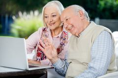 Elderly Couple Video Chatting On Laptop. Happy elderly couple video chatting on laptop while sitting at nursing home porch stock image