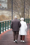 An elderly couple walking along a path. La Vella city, Andorra. An elderly couple, presumably husband and wife, is walking along a trail in the town of La Vella stock photo