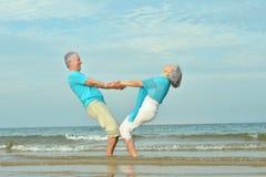 Elderly couple walking along  seashore Royalty Free Stock Photos