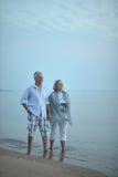 Elderly couple walking along  seashore Stock Photo