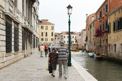 Elderly couple walking arm in arm through the ancient streets of. Venice in Italy Royalty Free Stock Photography