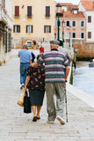 Elderly couple walking arm in arm through the ancient streets of Venice in Italy. Stock Image