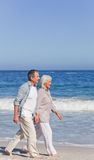 Elderly couple walking on the beach Royalty Free Stock Images
