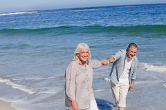 Elderly couple walking on the beach royalty free stock photography
