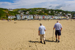 Elderly Couple Walking on Beach. Rear view of an elderly couple walking across a beach towards a seaside town on a sunny day. Aberdovey, Gwynedd, Wales, UK stock photography