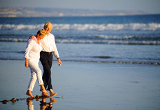 Elderly couple walking on beach Royalty Free Stock Photos