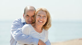 Elderly couple walking on the beach in summer stock photos