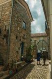 Elderly couple walking by cobblestone alley with stone houses. Alvoco da Serra, Portugal - July 15, 2018. Elderly couple walking by alley with old houses at stock photo