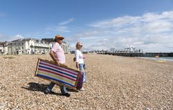 Day trippers on the beach in Southsea southern England. Elderly couple walking with a deckchair on a shingle beach. Southsea, England UK Royalty Free Stock Images