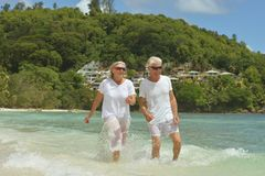 Elderly couple walking. Happy elderly couple walking on  tropical beach Stock Photos