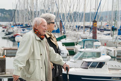 Elderly couple walking at the harbor Stock Photo