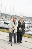 Elderly couple walking at the harbor Stock Image