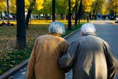 Elderly couple walking in park on autumn day stock photos