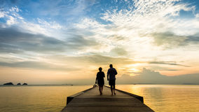 Elderly couple walking on the pier in the sea at sunset stock photography