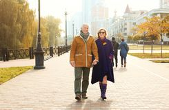 Elderly couple walking in the street. On autumn day Royalty Free Stock Photos
