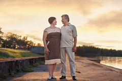 Elderly couple walking talking laughing at the sunset near the lake river royalty free stock photos