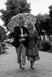 Elderly couple walking under an umbrella in the rain. Black and. White. True love. Talking Royalty Free Stock Photos