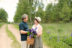 An elderly couple walks through the forest and a man gives a woman a woven basket with a bouquet of flowers of purple lupines stock photos