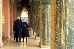 Elderly couple walks under the arcade Stock Photos